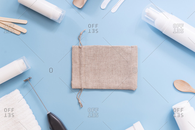 Kit to make your own cosmetics- cream- gunny bag on blue background