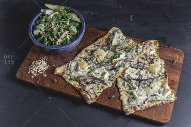 Tarte Flambee with camembert and thyme creme fraiche and red onion on chopping board- lamb's lettuce with pear in bowl
