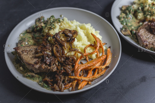 Beef sirloin steak with mushroom-mustard sauce- mashed potatoes- braised onions and carrot strips