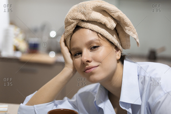 Portrait of smiling young woman with  hair wrapped in a towel in the kitchen