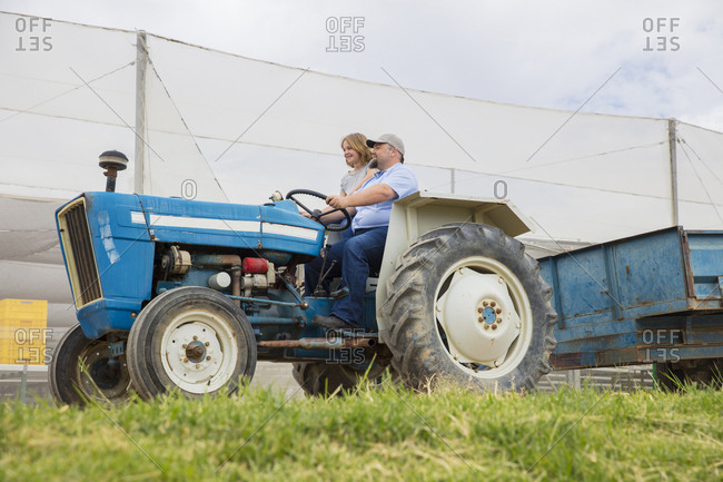 Farmer showing his daughter- how to drive a tractor