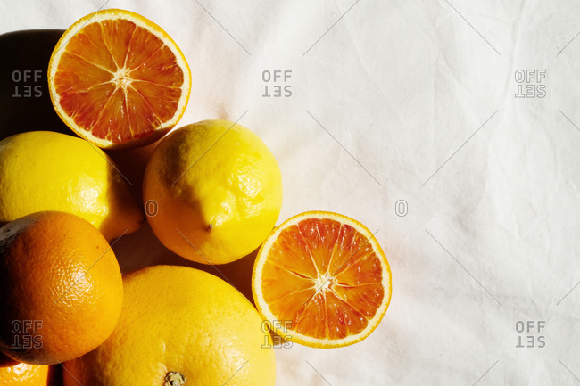 Whole and sliced oranges on white background.