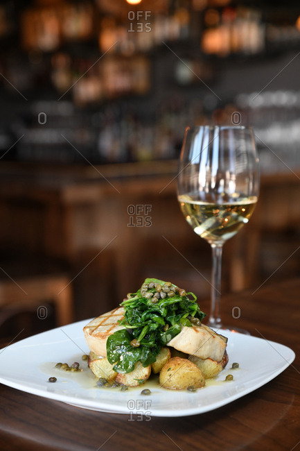 Wine served with gourmet swordfish meal in a restaurant