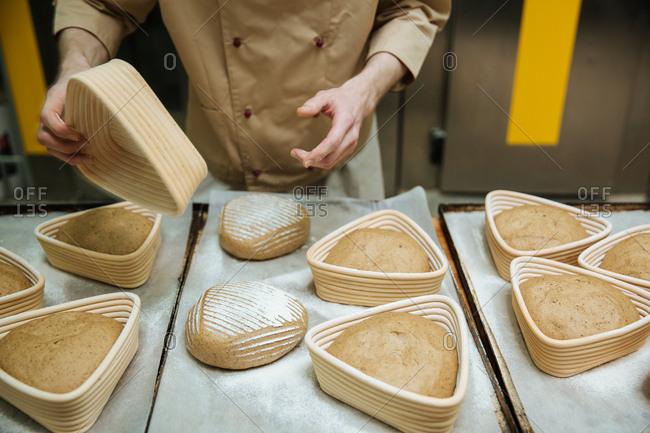 Baker preparing loaves of bread