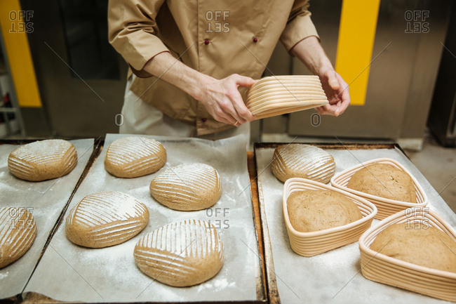 Baker shaping loaves of bread in a bakery