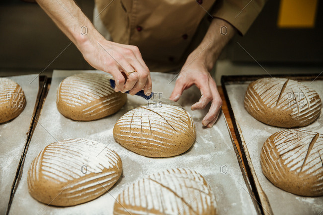 Baker preparing artisanal loaves of bread in a bakery