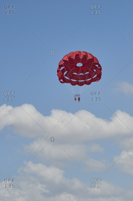 Albufeira, Portugal - September 28, 2018: Low angle view of people parasailing off the coast of Albufeira, Portugal