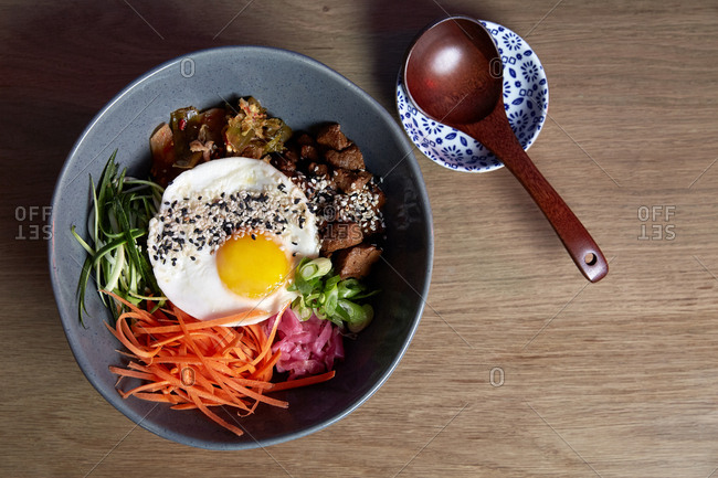 Japanese rice bowl with beef and vegetables topped with a fried egg