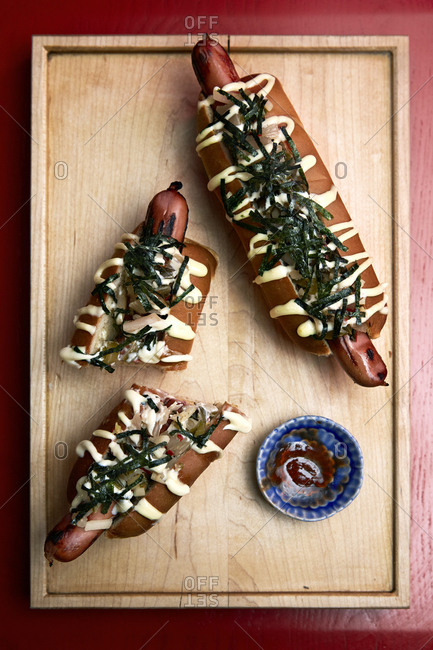 Japanese style hotdogs on a wooden tray and red background