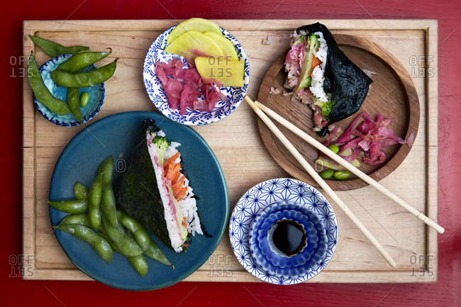 Vegetarian hand roll with pickled ginger and soy sauce on a tray