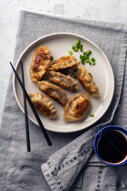 Fried gyoza dumplings with pork served with soy sauce and scallions