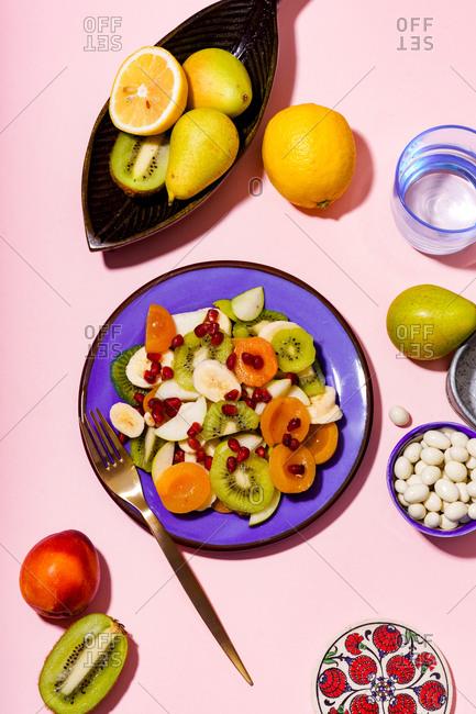 Overhead shot of fruit salad with kiwi, banana and pomegranate seeds