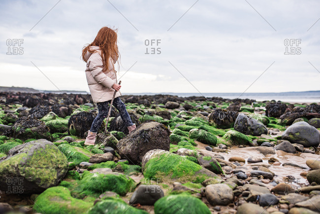Girl with a stick on rocks on the beach