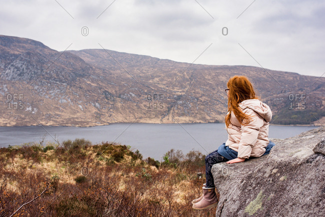 Girl looking at a lake in the mountains