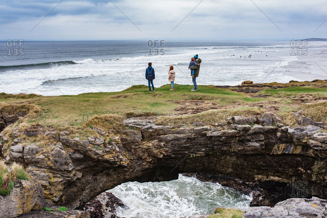 Family on a rock formation bridge looking at the sea