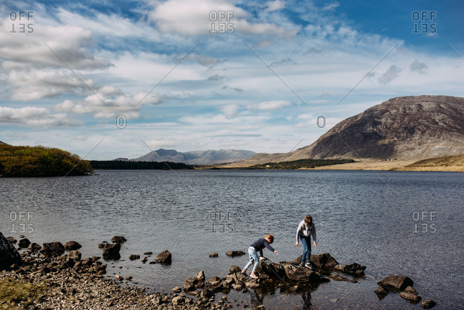 Boy and girl walking on rocks at a lake in the mountains