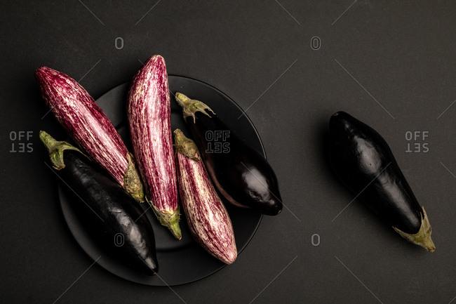 Set of fresh ripe eggplants placed on black table