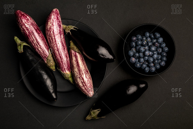 Set of fresh ripe eggplants and blueberries placed on black table