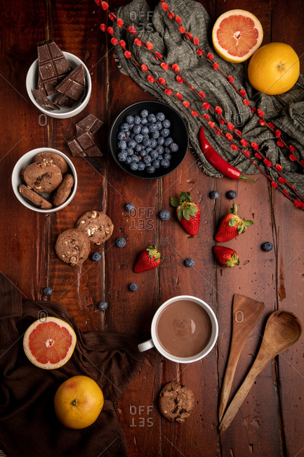 Mug of tasty hot chocolate placed on timber tabletop near assorted desserts and fruits for breakfast