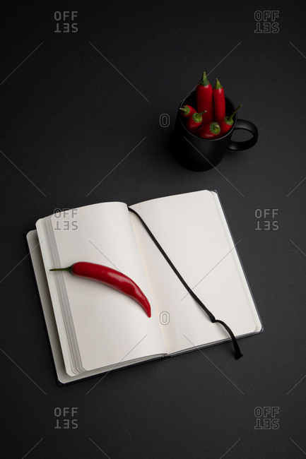 Mug of hot red chili peppers placed on black background near open notepad with blank pages