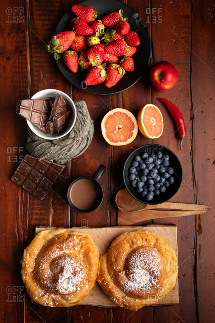 Fresh hot beverage and various tasty breakfast food placed on lumber tabletop in morning