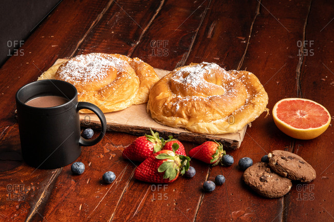 Fresh red apple and ripe blueberries placed on timber tabletop near mug of aromatic hot beverage and delicious bun for breakfast in morning