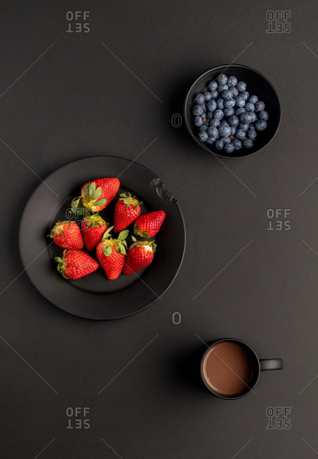 Various fresh fruits and mug of aromatic hot beverage for breakfast placed on black background