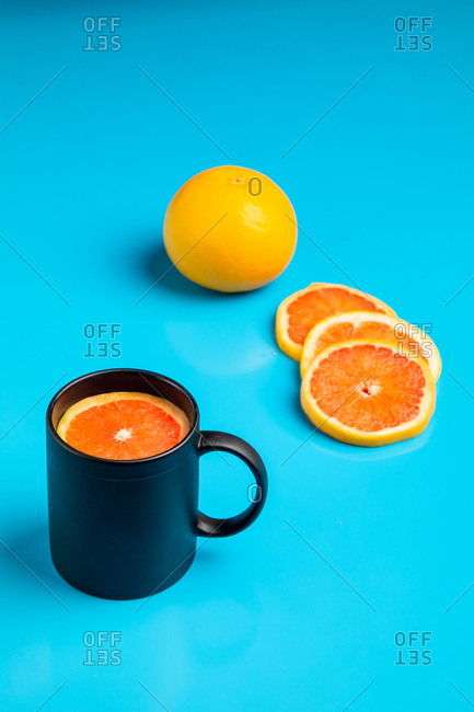 Black mug with slice of fresh ripe citrus for breakfast placed on bright blue teal background
