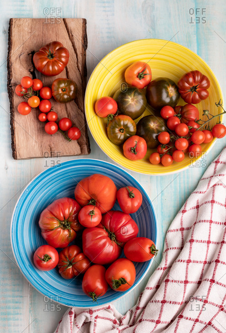 Cloth napkins placed on wooden table near ceramic bowls and lumber board with fresh red tomatoes