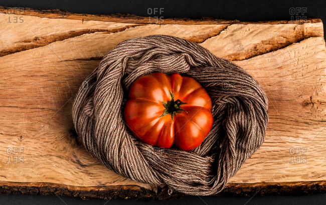 Fresh ripe tomato and fabric napkin placed on piece of wood against black background