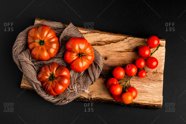 Fresh ripe tomatoes and fabric napkin placed on piece of wood against black background