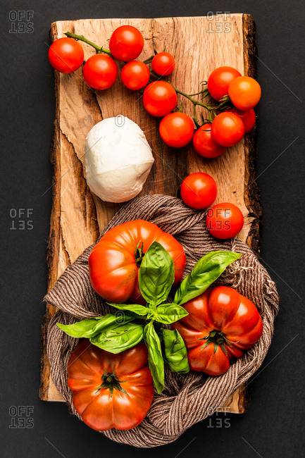 Fresh ripe tomatoes, mozzarella, and fabric napkin placed on piece of wood against black background