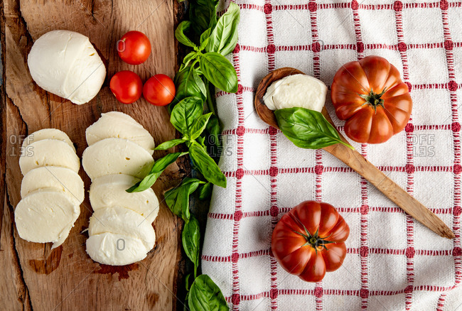 Fresh tomatoes and mozzarella cheese with basil leaves for salad placed on wooden board and fabric napkin