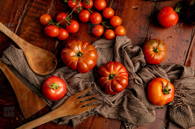 Set of assorted fresh tomatoes and fabric napkins placed on lumber tabletop in kitchen