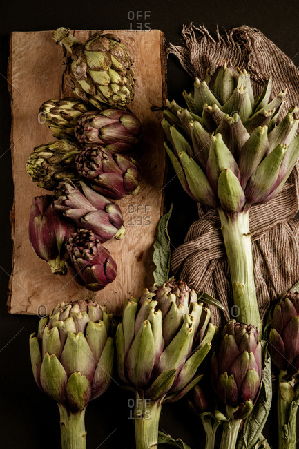 Fresh ripe artichokes placed on black background with napkin and wooden table