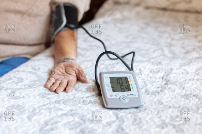 elder man checking his arterial pressure with machine