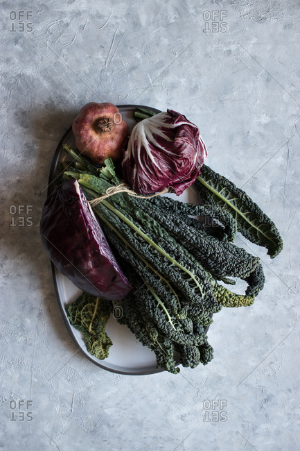 From above small pomegranate placed on plate near bunch of green kale leaves and fresh red cabbage on gray tabletop