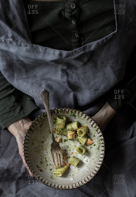 Anonymous woman holding a bowl of palatable pasta paccheri with fresh kale pesto and ground peanuts