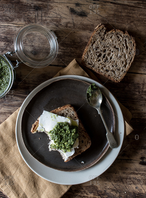 From above plate with tasty rye toast with cheese and fresh pesto placed on timber tabletop