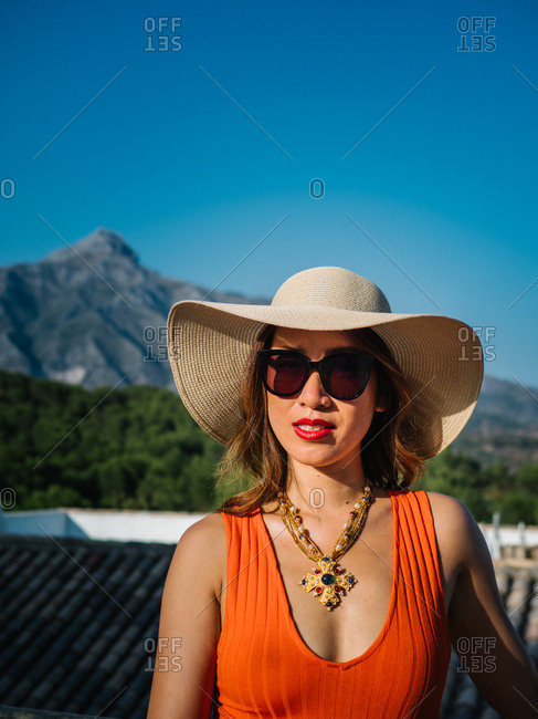 Young classy chinese woman in panama hat and sunglasses enjoying a bright summer day