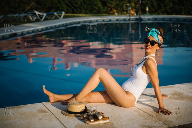 Young rich chinese woman sunbathing by a pool at a luxurious resort