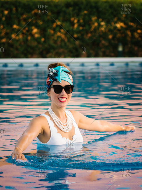 Young rich chinese woman relaxing swimming in a pool at a luxurious resort