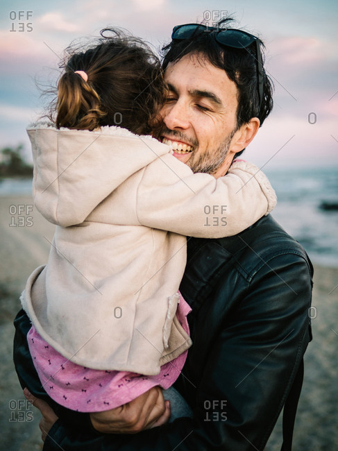 cute scene of dad holding and hugging her little daughter at the beach in winter