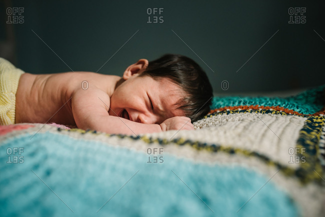 Cute shirtless baby lying on warm knitted blanket and crying loudly in cozy nursery