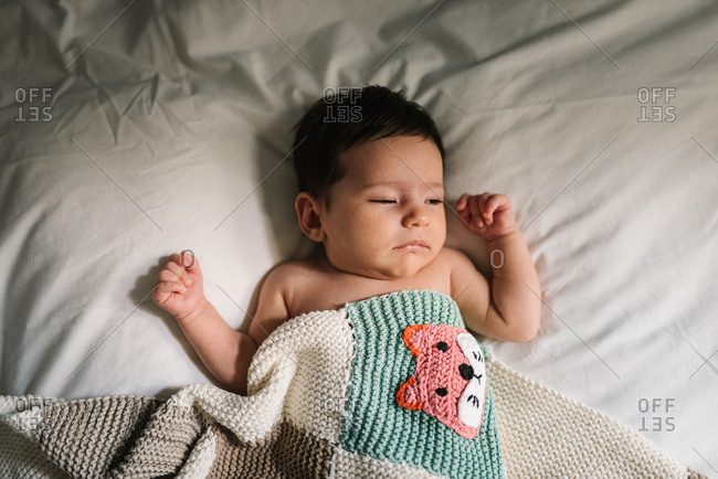 Adorable newborn baby lying under warm knitted blanket and peacefully sleeping on soft bed at home
