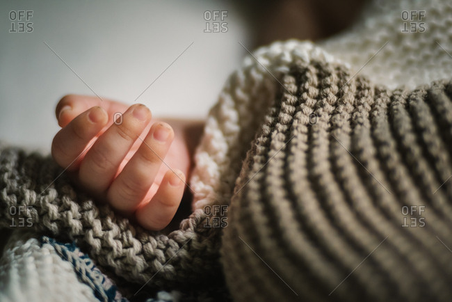 Close-up hand of anonymous sleeping baby lying under soft knitted blanket in nursery
