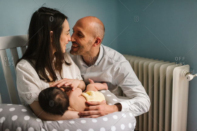 Cheerful adult man hugging smiling woman and baby during breastfeeding in cozy nursery at home