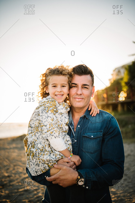 Middle aged man with her daughter at sea shore smiling and hugging each other