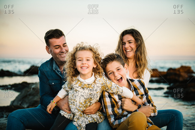 Middle aged man an woman with children at sea shore smiling and hugging each other