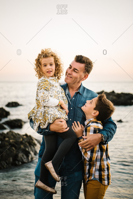 Middle aged man with her children at sea shore smiling and hugging each other
